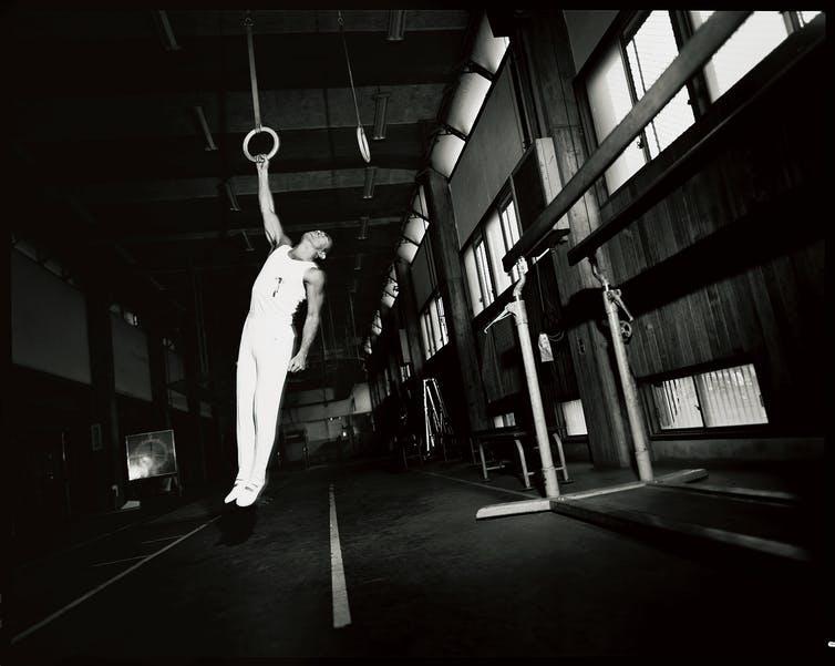 Yukio Mishima, vêtu de blanc, est suspendu, ensanglanté, à un anneau immobile.