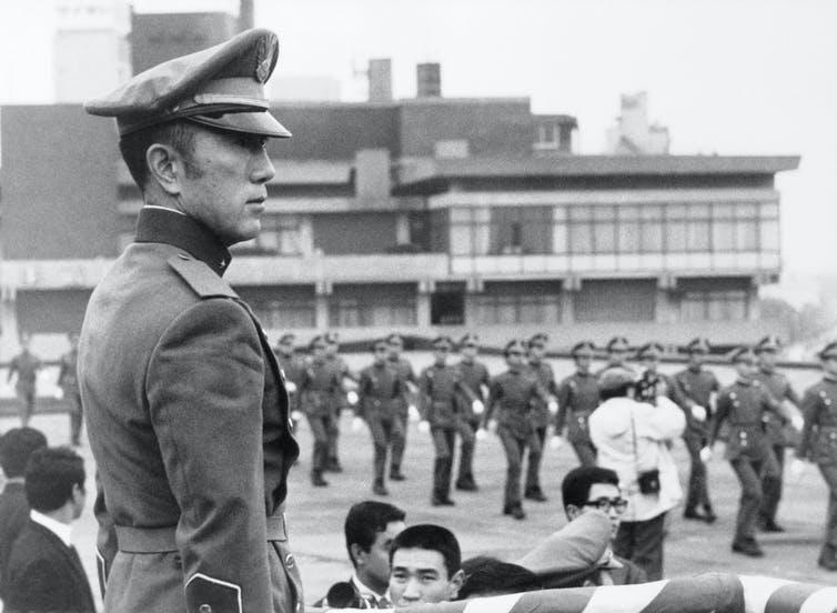 En uniforme militaire, Mishima observe les marcheurs.