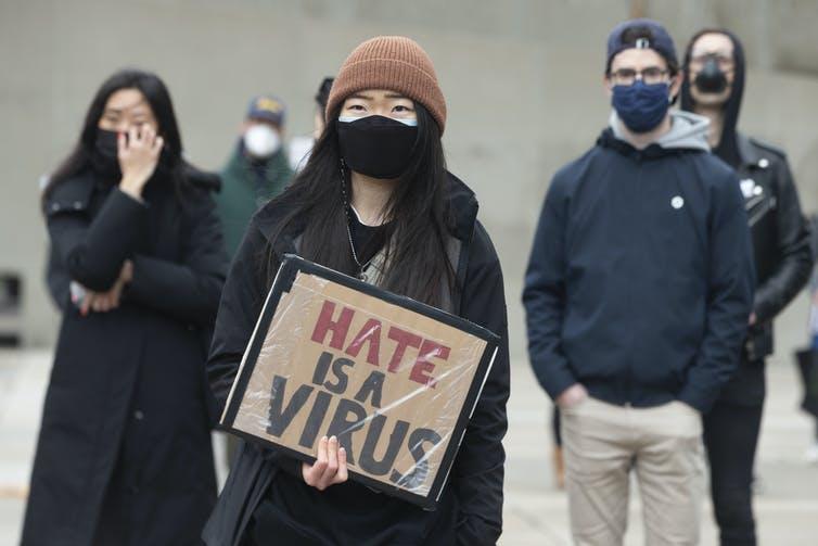 Une femme se tient debout en tenant une pancarte sur laquelle on peut lire «Hate is a virus»